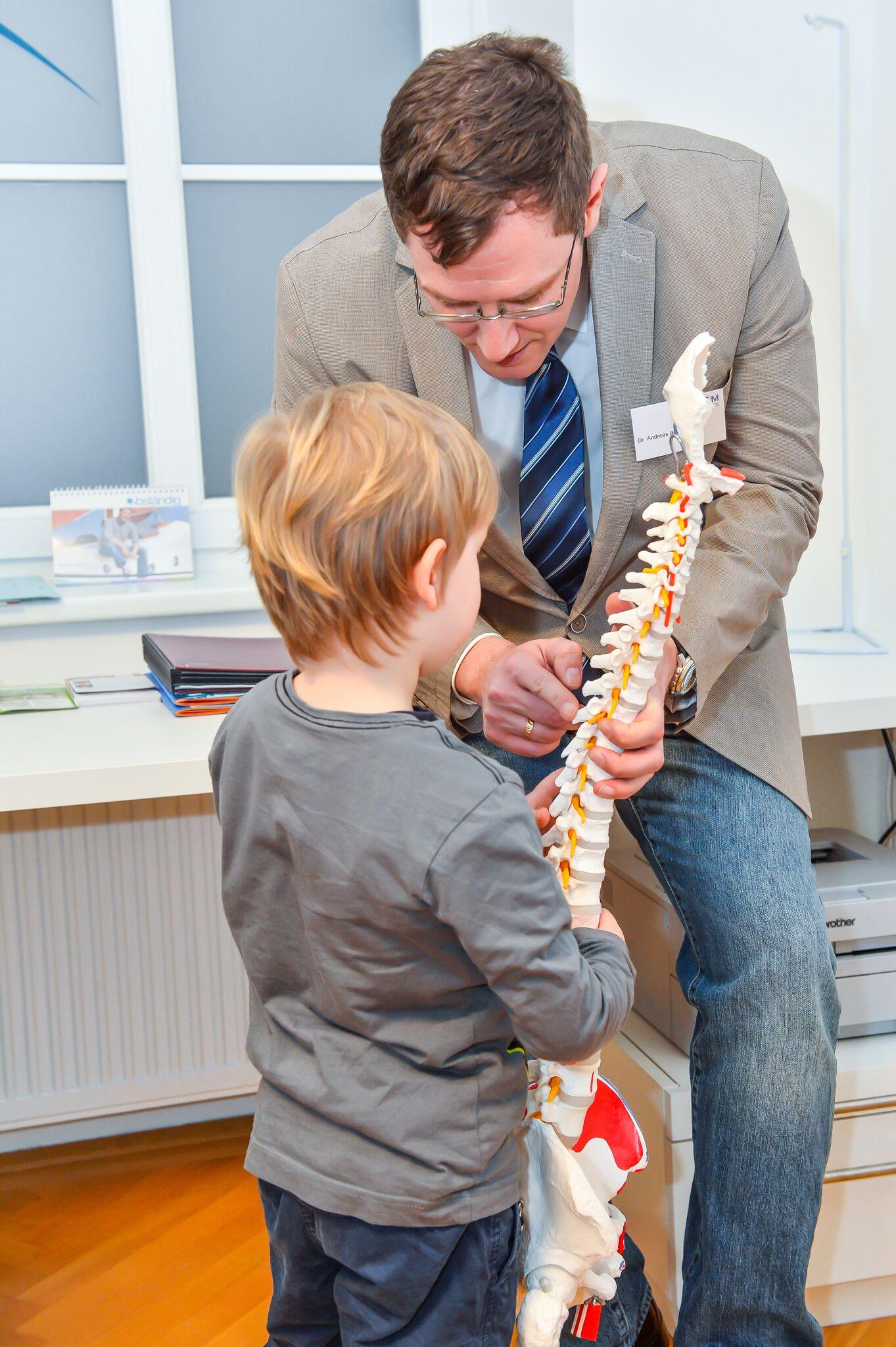 Dr. Birner erklärt einem Kind die Funktion der Wirbelsäule